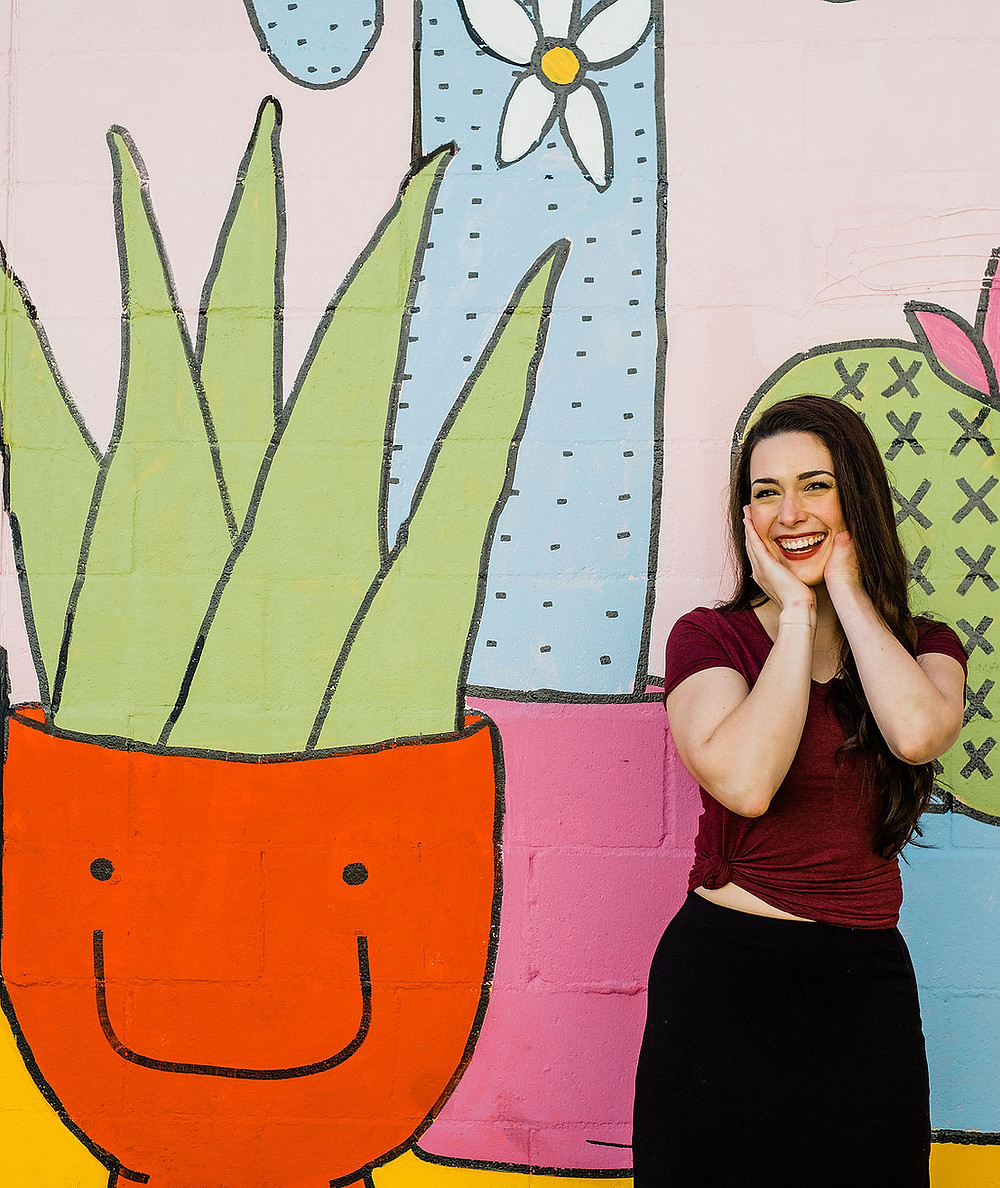 Sarah Tuberty poses, with her head in her hands, in front of a floral mural of large smiling succulents.