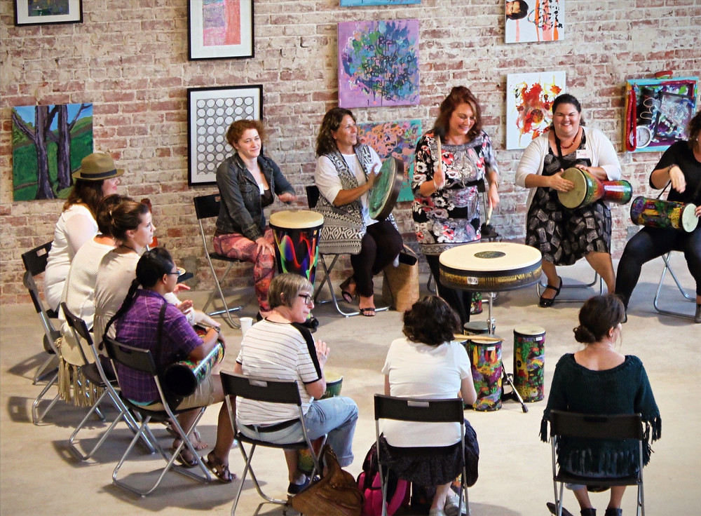 Helen Dolas leads a music therapy drum circle in person with adults in an art gallery