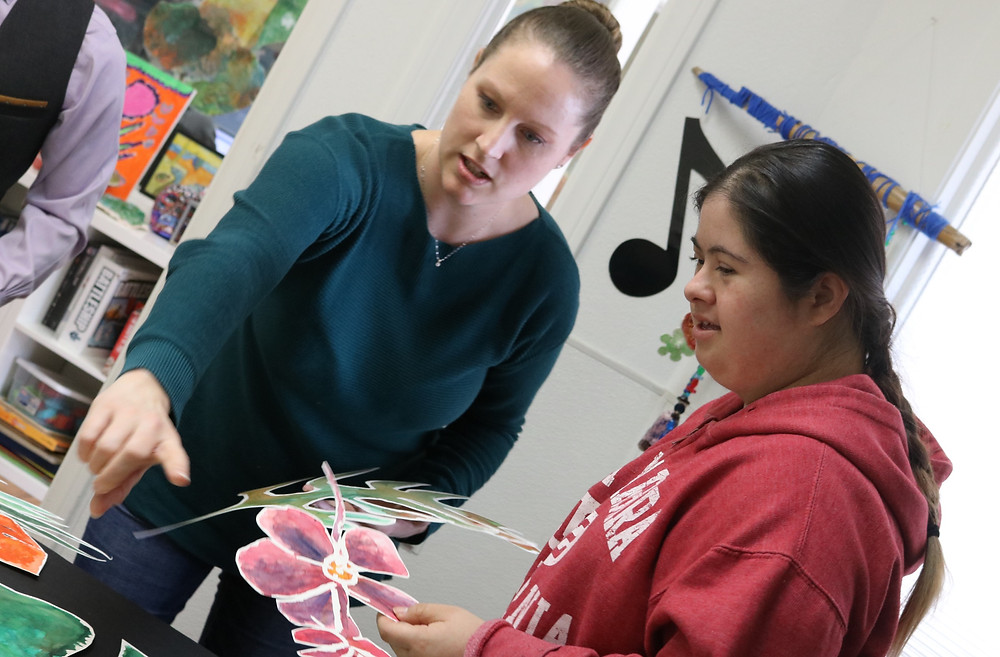 Two women, art therapist Katie on the left and resident artist Julianna on the right working on floral watercolor collage