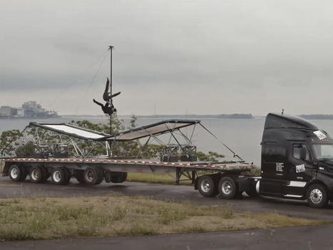 Acrobats jump on trampolines while the trailer is pulled by a Truck'N Roll truck