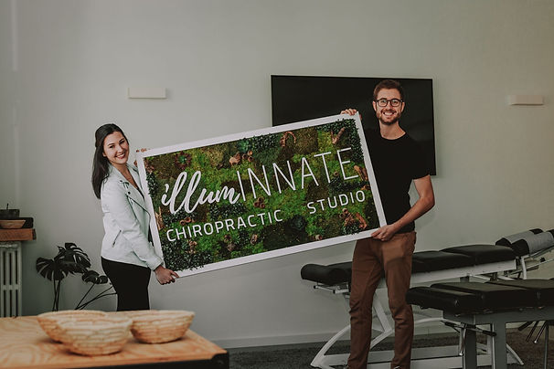 illumINNATE chiropractors, Kelli and Francisco Turelli, holding a logo sign