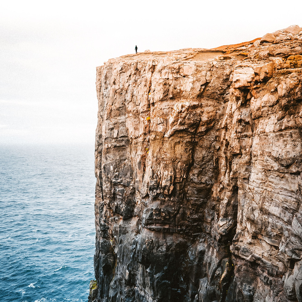 person standing on edge of huge cliff looking over the ocean
