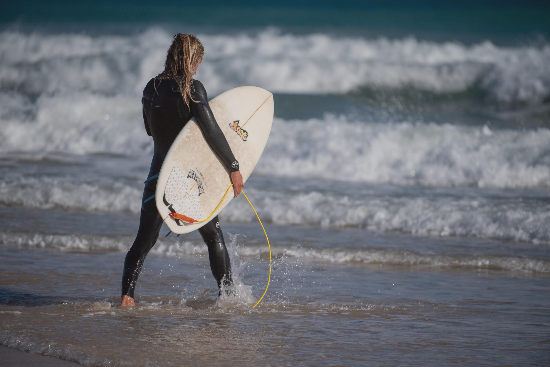 Surfer am Weg ins Wasser