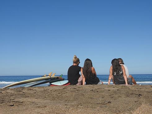 Vier Surfer sitzen am Strand und schauen aufs Meer