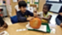 2 students holding a pumpkin