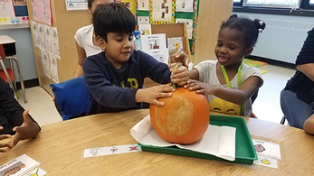 2 students holding a pumpkin