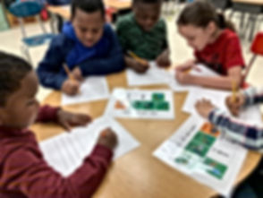 Students completing a science activity in a group at a table.