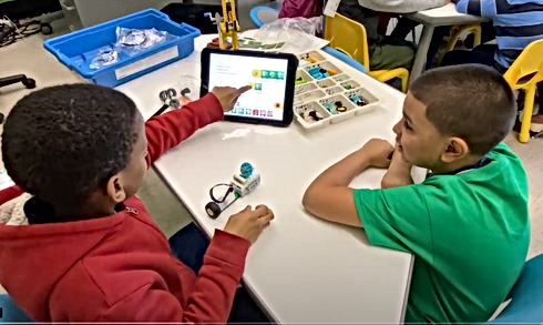 2 students coding using an iPad and robot