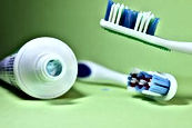Tooth brushes and tooth paste on green background