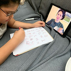 Student writing letters during her Occupational Therapy session on the ipad.