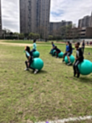 Students bouncing on green medicine balls on the school track