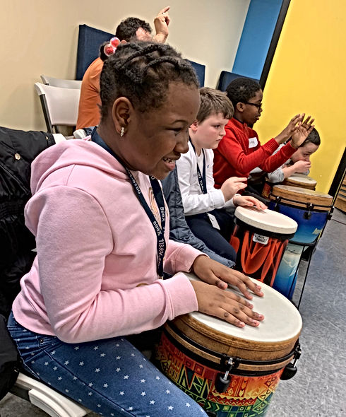 Students playing the drum in music class while singing.