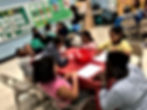 Students working in groups at a table with their teacher