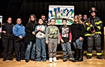 Art teacher and PS596X students posing with first responders and their artwork.