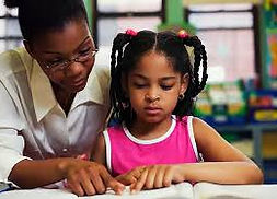 Teacher working with student on reading assignment