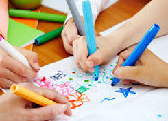 photo of kids drawing with markers on white paper.