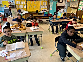 Students from class V05 sitting at their desks and sharing their creative writing activity.