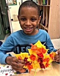 Student posing with their art project featuring leaves they made using fall colors.