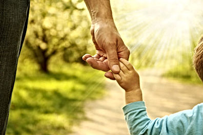 A parent holding a child'shand while walking in the sunshine.
