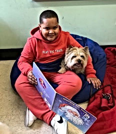 Benny the Reading Dog sitting wth a boy holding a book.