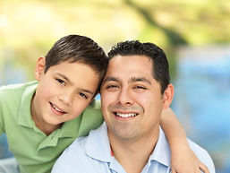 Boy with his arm around his father smiling.
