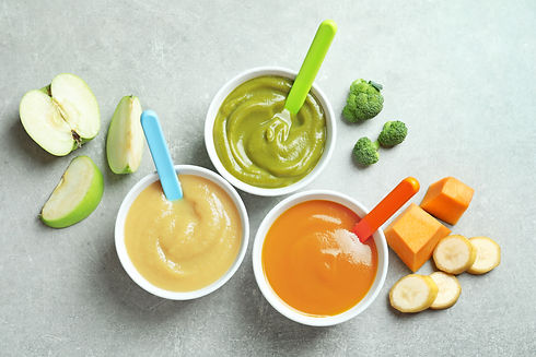 Bowls with baby food on grey background.