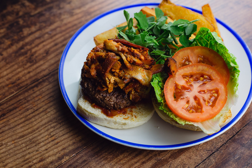 A photo of our new louisiana pork belly burger.
