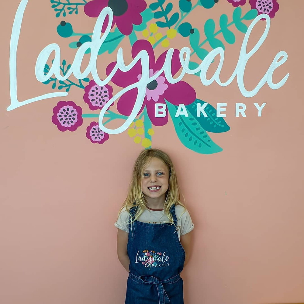 Ladyvale logo on wall with child standing in front