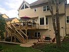 backyard landsape design with deck an fire pit by Bailey Construction & Landscape Group, Inc