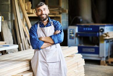 Portrait of mature bearded carpenter pos