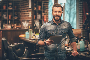 Keeping business on top with digital technologies. Cheerful young bearded man looking at c