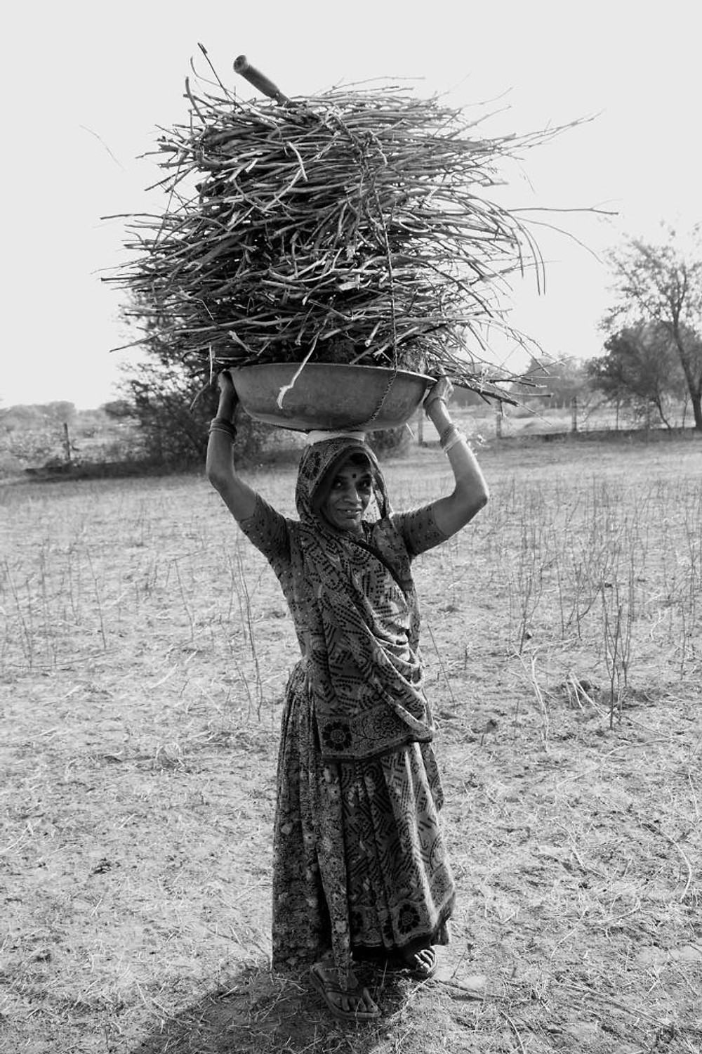 woman carries firewood back to her home to cook dinner ieclectica Photograph by Ashwathi