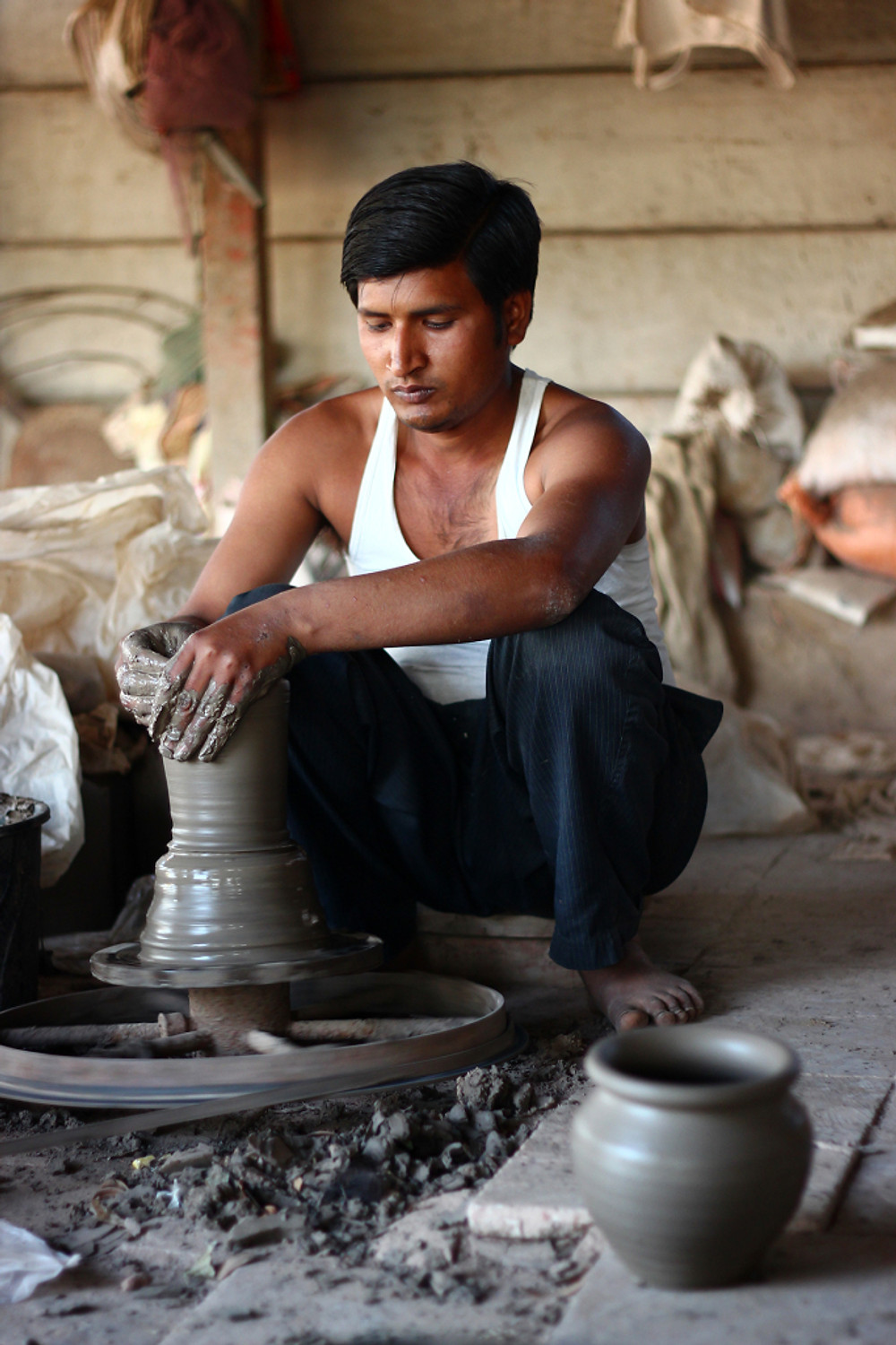 Man moulding clay to make pots in a workshop in gandhinagar gujarat india ieclectica Photograph by Ashwathi