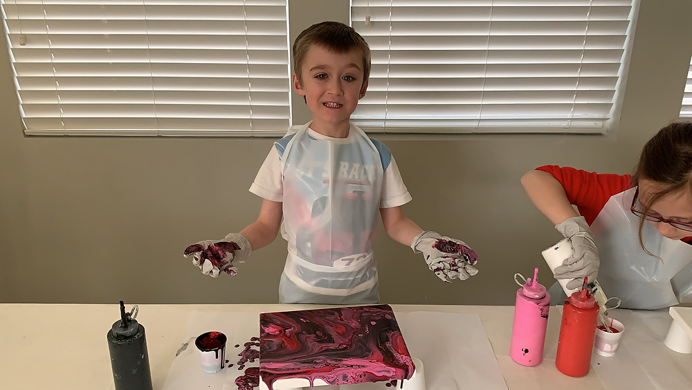 "This paint kit had black, pink and red in it. I think it turned out cool and it wasn't too ""girly"" for him. He put all the paint in a cup and poured it on the canvas and this is how it turned out! Masterpiece."