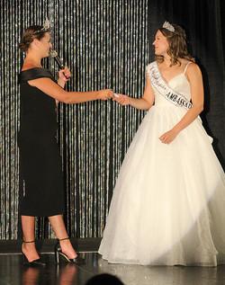 Aquatennial Princess Amber Watkins handing queen's charm to Anna Lucas