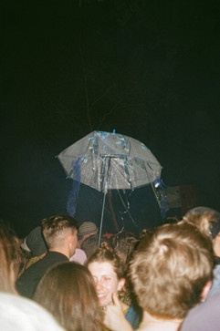 Why do people bring umbrellas to a festival?