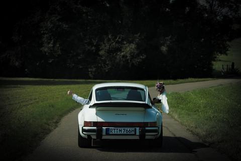 Brautpaar fahrend im Porsche