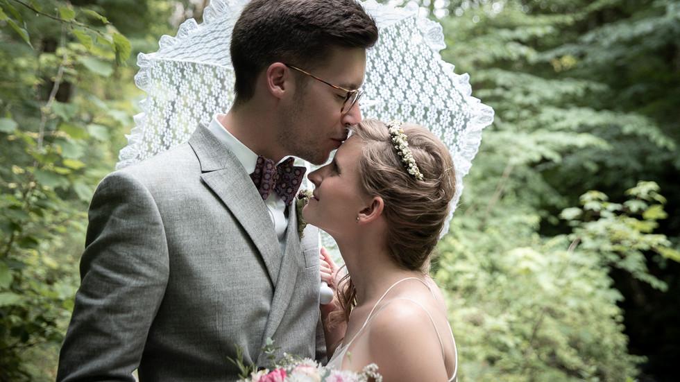 Bräutigam küsst Braut auf Strin