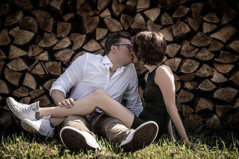 Küssendes Pärchen vor Holz