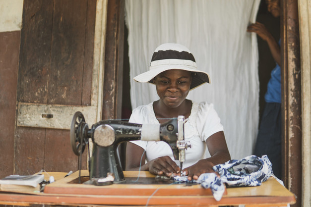 """Loan recipient Lovely Chery, 22, works on a garment for a client. She has been apprenticing at the house of a friend so that she can learn the trade. """"My family doesn't have money so I had to stop high school. [tuition is needed to go to high school in Haiti]  I just have my final year of high school to go. In the meantime I'm helping my mom, doing different things [to earn money]. Later, I want to be a nurse."""""""
