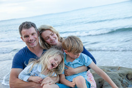 Location fun family photo at the beach with parents and children by professional photographer Angela Scott
