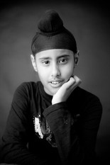 A boy poses in a close-up studio portrait in black and white in Angela Scott's Auckland studio