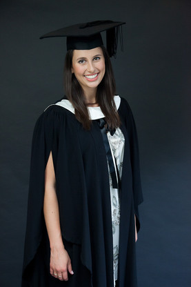 Woman smiling and standing in graduation photoshoot in studio with cap and gown by professional photographer Angela Scott