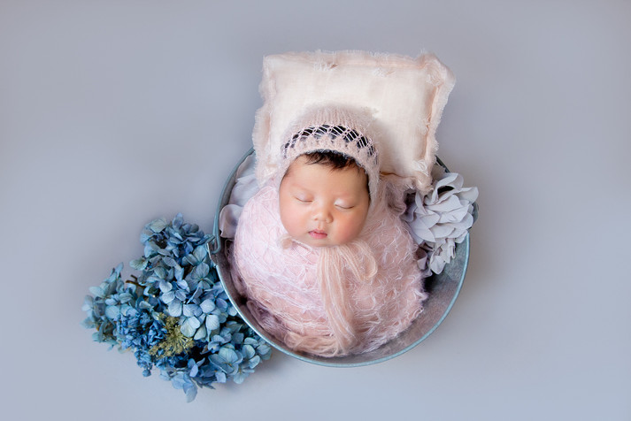 Newborn baby girl in a bowl in a studio photoshoot