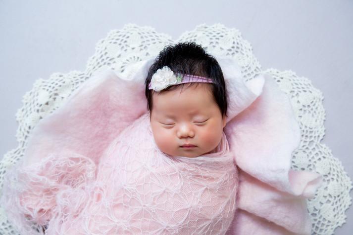 Sleeping newborn baby infant photoshoot in pink crochet blanket in the studio
