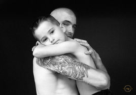 Black and white studio portrait of father and son hugging