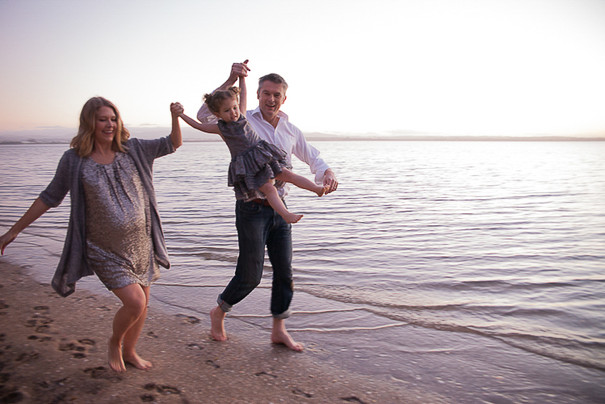 Fun family beach location photoshoot with child swinging between parents