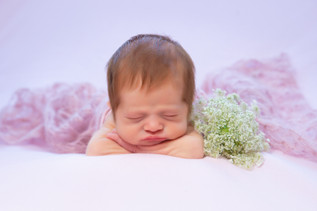 Newborn infant asleep with flowers and pink blanket in a professional studio photo shoot
