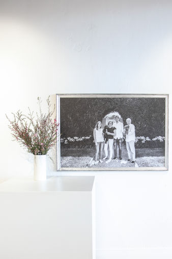 Black and white framed portrait shown hanging on a white wall