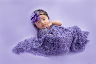 Baby wrapped in a purple blanket looking at the photographer while being photographed